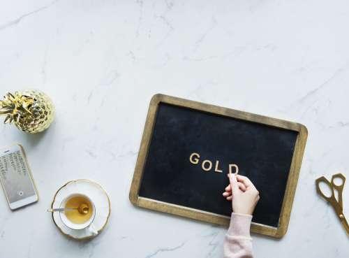 """Flatlay Of A Model Spelling """"Gold"""" On A Blackboard Photo"""