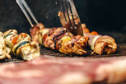 Flipping Chicken And Veggie Kabob On Grill Photo