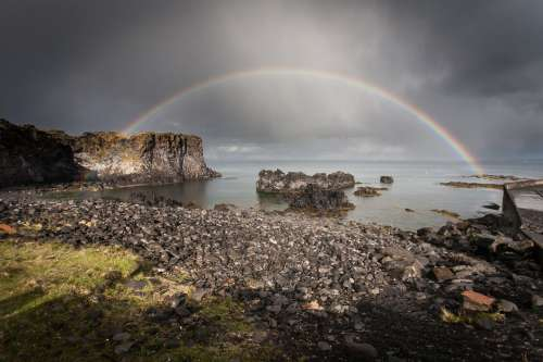 Full Rainbow Over Rocks And Water Photo
