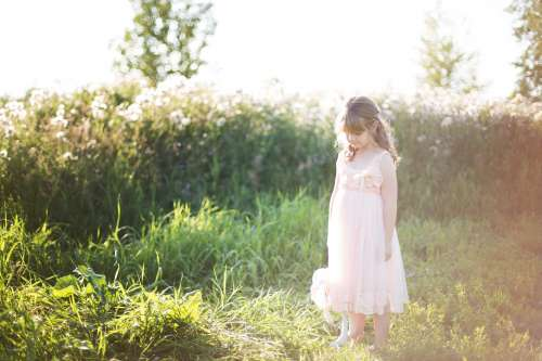 Girl In Pink Looking Down At Grass Photo