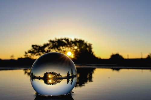 Glass Ball On Water At Sunset Photo