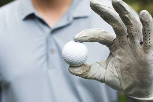 Golfer Holds Golf Ball Photo