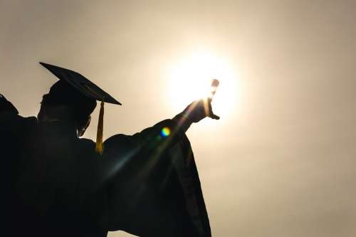 Grad Student Celebrating Diploma Up In Sun Photo