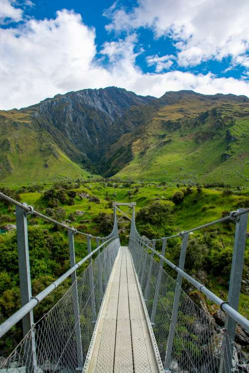 Hanging Bridge Over New Zealand Fields And Mountain Photo