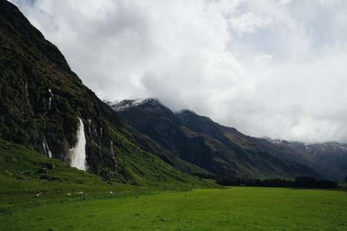 Lush Green Fields By Mountains And Waterfall Photo