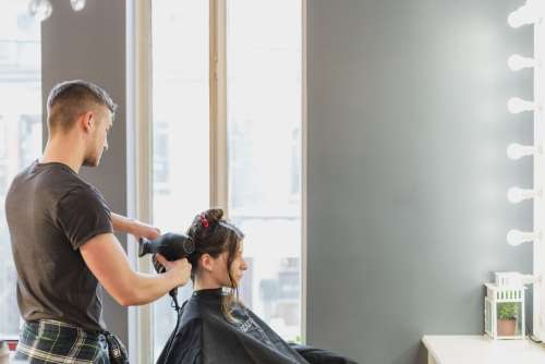 Male Stylist Cutting Hair At Salon Photo