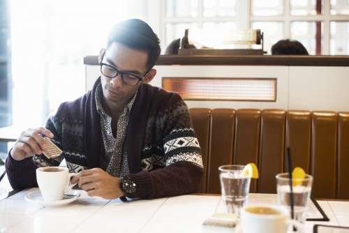 Man Adds Sugar To Coffee In Cafe Photo
