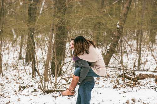 Man Carries His Girlfriend On His Back Threw The Snow Photo