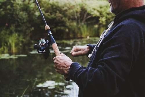 Man Reeling In On Fishing Rod Photo