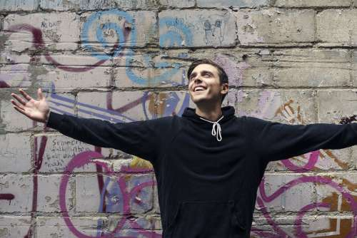 Man Smiles With Open Arms In City Photo