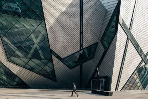 Man Walking In Front Of Modern Building Photo