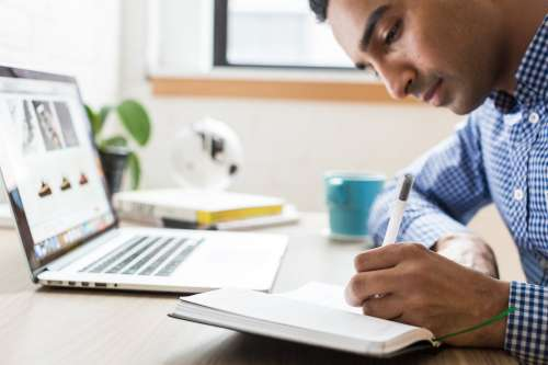 Man Writing In Notebook Photo