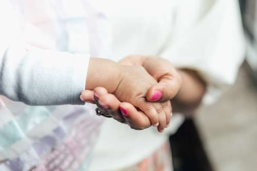 Mother Holding Babies Hand Photo
