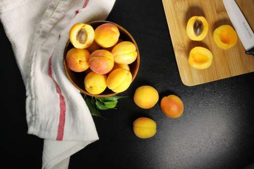 Overhead Shot Of Fresh Apricots Being Halved And Pitted Photo