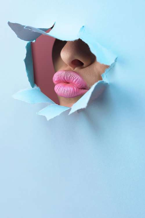 Pink Lipstick Through Bright Blue Paper Photo