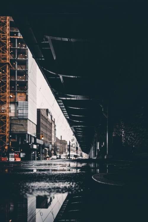 Puddle Water Reflects Urban Bridge Photo