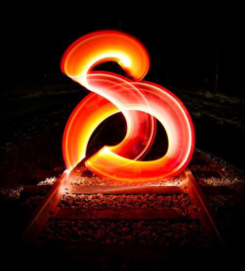 Red Light Streaks Above Rail Tracks Photo
