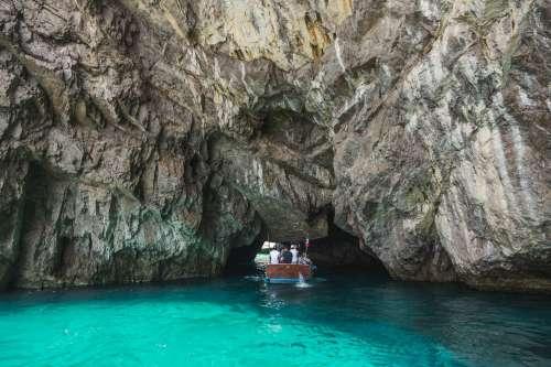Small Boat Sailing Under Rocks Photo