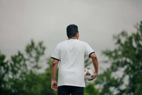 Soccer Player Holding Ball Looking Out Photo
