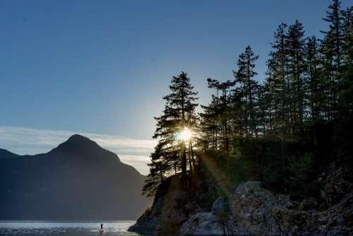 Sunrise Glaring Through The Trees As Man Takes To Water Photo