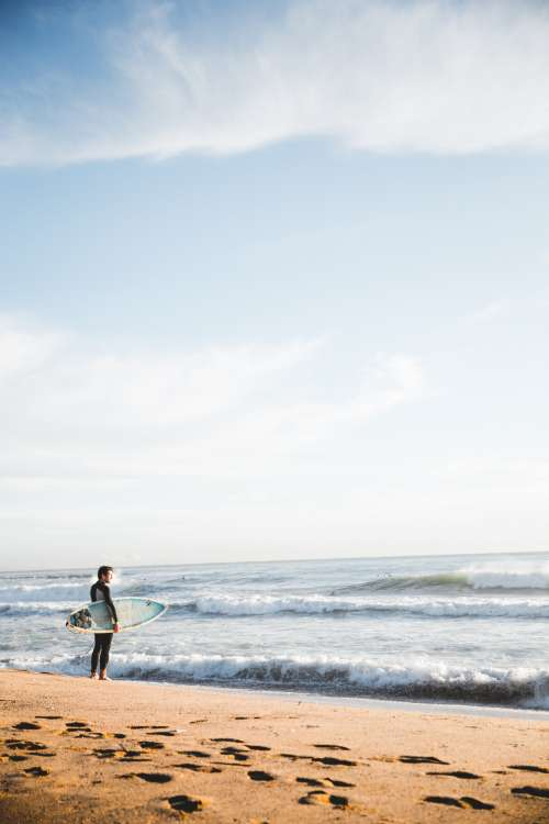 Surfer Standing By Ocean Photo