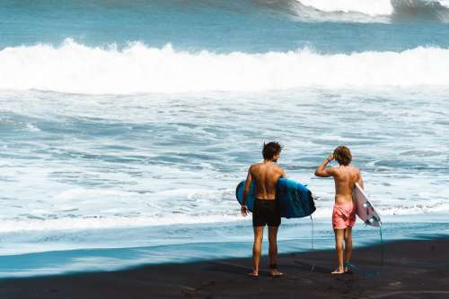 Surfers Stand On Shore Photo