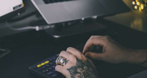Tattooed hands Typing On Office Keyboard Photo