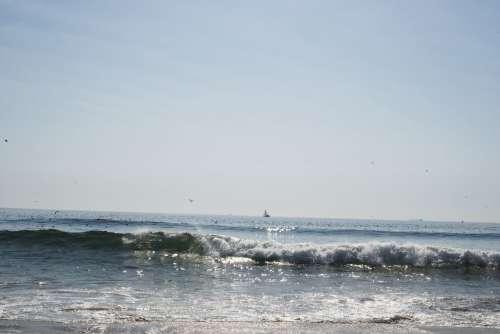 The Sea Crashing Into Shore On A Sunny Day Photo