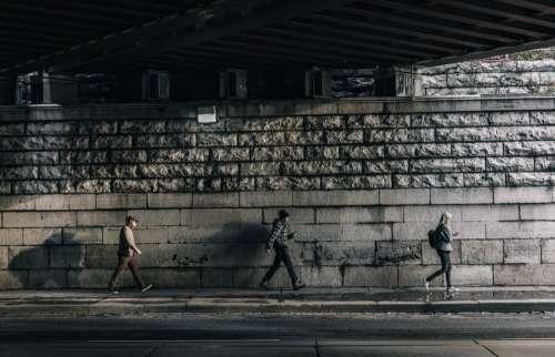 Three Urban Pedestrians Walk Under Bridge Photo