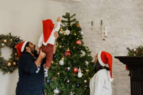 Toddler Helps Decorate The Christmas Tree Photo