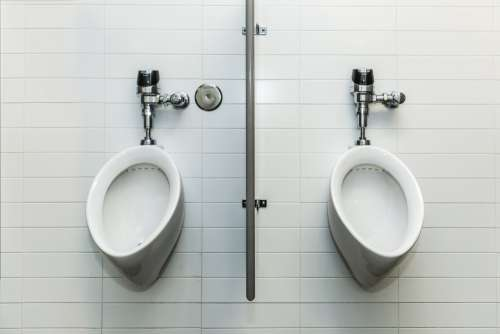 Two Urinals On White Tile Wall Photo