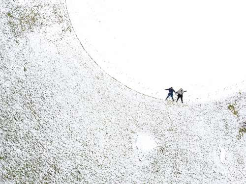 Two Women Make Snow Angels In A Snowy Ball Field Photo