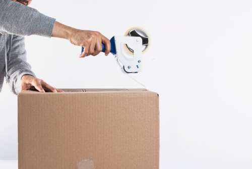 Using A Tape Dispenser To Close Up A Box Photo