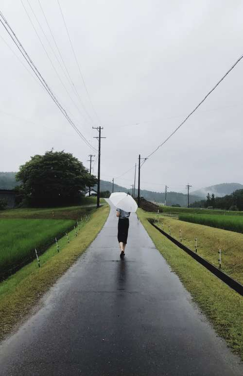 Woman Carries Umbrella Along A Lonely Road Photo
