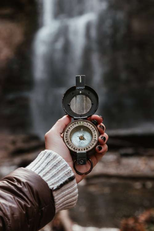 Woman Checks Compass At Waterfall Photo
