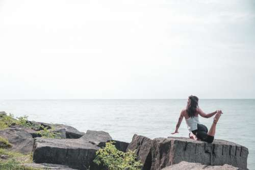 Woman Does Yoga By The Water Photo