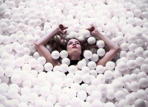 Woman Floating With Arms Raised In Ball Pit Photo