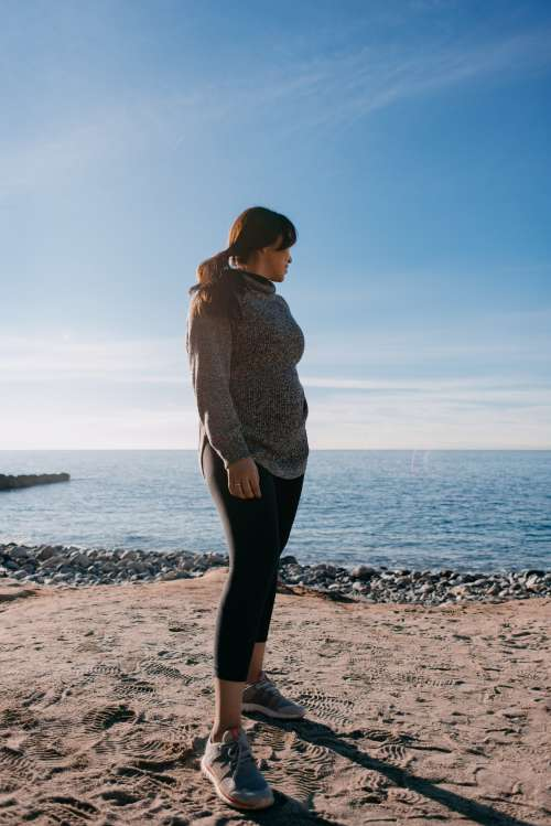 Woman Glances Back At The Sea Behind Her In The Morning Light Photo