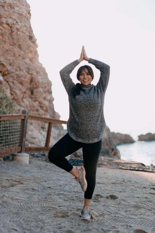 Woman Holding A Yoga Position On The Beach Photo