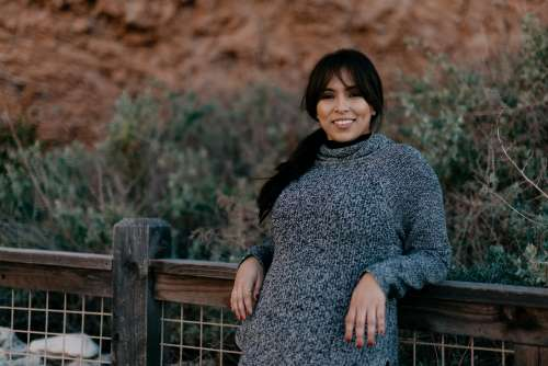Woman In A Sweater Smiles As She Leans Against A Fence Photo