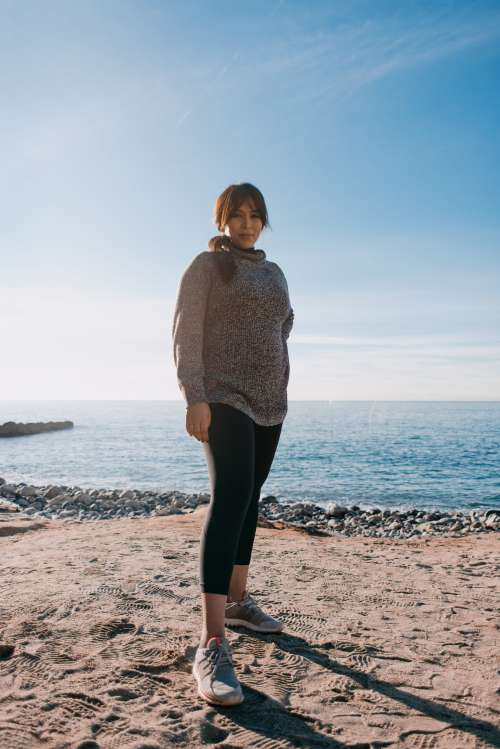 Woman In A Sweater Stands On A Beach In The Morning Photo