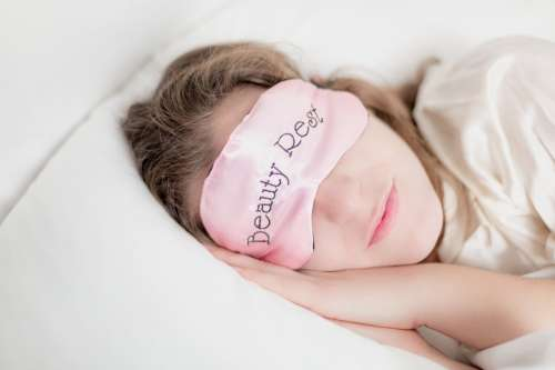 Woman In Beauty Rest Mask In Pillow Photo