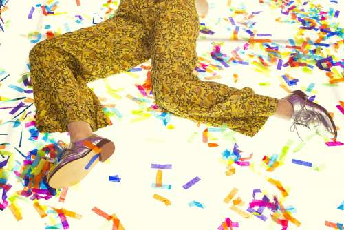Woman In Silver Leather Oxfords Laying In Confetti Photo