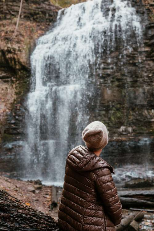 Woman In Winter Fashion Sits By Foot Of Waterfall Photo