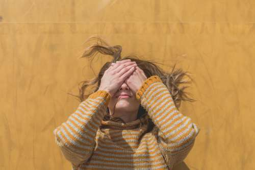 Woman In Yellow Hides Face Photo