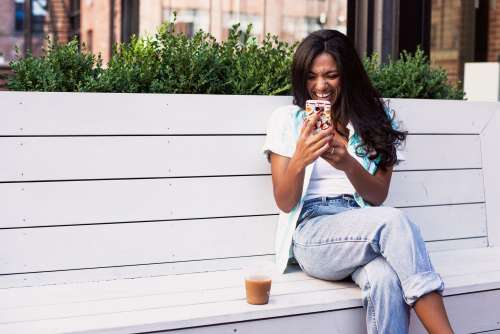 Woman Laughs At Mobile Phone Photo