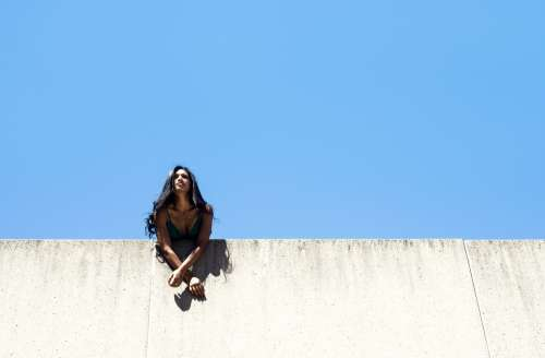Woman Leans Over City Wall With Blue Sky Photo