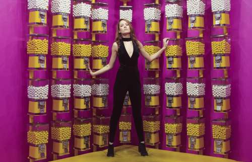 Woman Poses Against A Wall Of Gumball Machines Photo