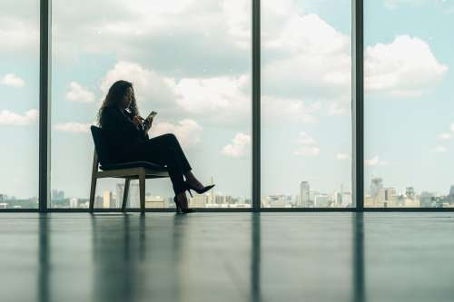 Woman Sitting On Phone In Modern Office Chair Photo