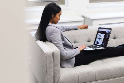 Woman With Laptop On Couch Photo